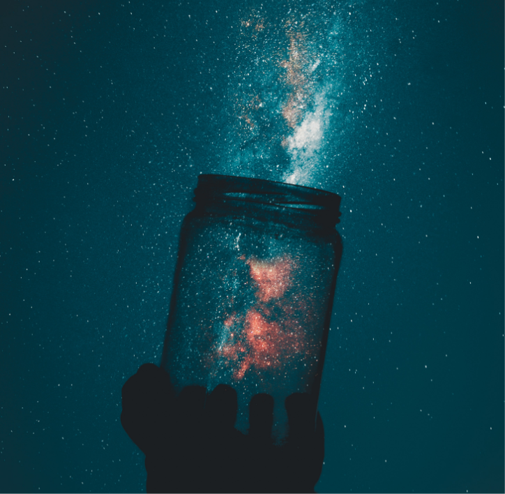 Hand holding jar filled with stars against galaxy background